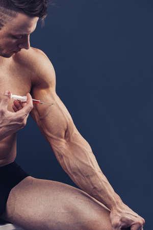 a muscular man with a syringe Foto de archivo