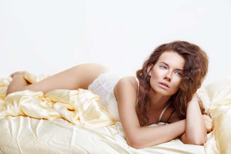 Attractive woman in white lingerie lying in the seductive pose on bed Reklamní fotografie