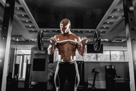Muscular man working out in gym doing exercises with dumbbells at biceps, strong male torso abs