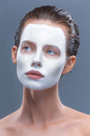 Beautiful girl is applied a white cosmetic mask from black dots. Isolate, studio