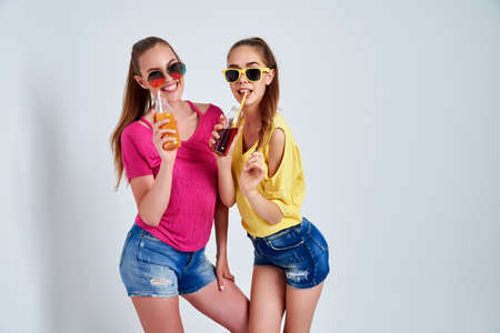 Close-up portrait of two person nice cute cool fascinating lovely attractive charming cheerful girls in casual clothes with beverage isolated over white background