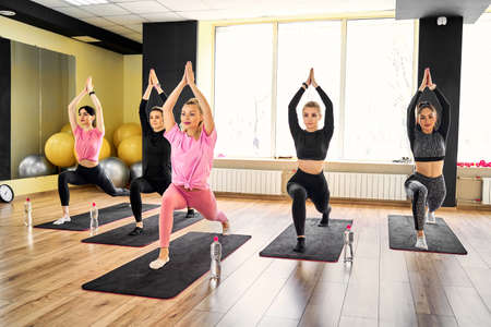 Group of young sporty attractive people practicing yoga lesson with instructor, standing together in Virabhadrasana 1 exercise, Warrior one pose, working out