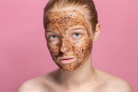 Facial skin scrub Coffee grounds mask on the face of a beautiful young woman Foto de archivo