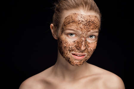 Skin scrub Coffee grounds mask on the face of a beautiful young woman
