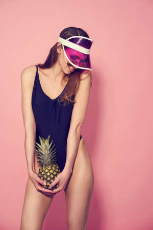 Woman in plastic cap visor, sunglasses and swimwear with pineapple on pink background. Summer season