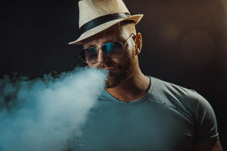 Bearded brutal male in hat and sunglasses smoking a vapor cigarette as an alternative to tobacco. Studio shot on dark background.