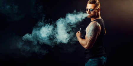 Bearded brutal male in sunglasses smoking a vapor cigarette as an alternative to tobacco. Studio shot on dark background.
