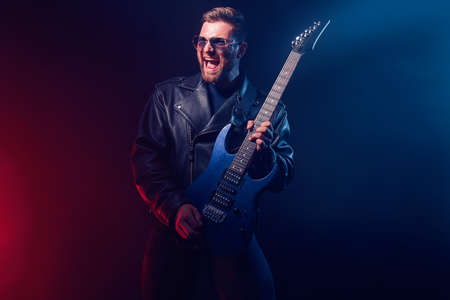 Brutal bearded Heavy metal musician in leather jacket and sunglasses is playing electrical guitar. Shot in a studio on dark background with smoke 免版税图像
