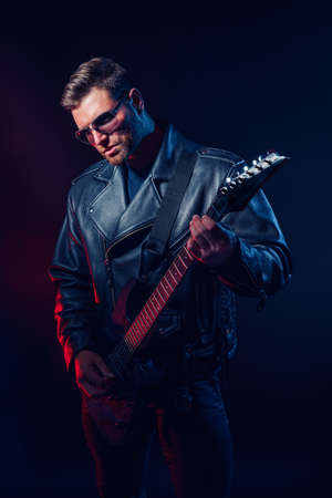 Brutal bearded Heavy metal musician in leather jacket, cap and sunglasses is playing electrical guitar. Shot in a studio on dark background