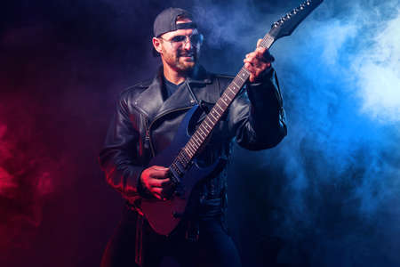 Brutal bearded Heavy metal musician in leather jacket and sunglasses is playing electrical guitar. Shot in a studio on dark background with smoke