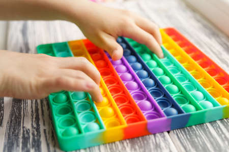 Trendy popular silicone colorful anti stress pop it toy . Close up. Someone push sensory popit.