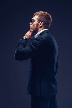 Side view of a Fashion bearded young serious man in sunglasses, luxury suit with one hand in pocket, other is on the chin 免版税图像