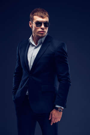 Fashion bearded young serious man in sunglasses, luxury suit with one hand in pocket