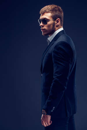 Side view of a Fashion bearded young serious man in sunglasses, luxury suit with one hand in pocket