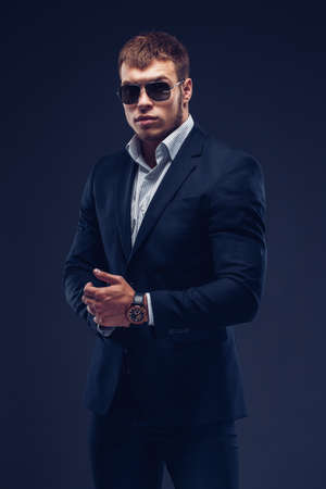 Fashion bearded young serious man in sunglasses, luxury suit looking at camera on dark background