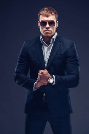 Fashion bearded young serious man in sunglasses, luxury suit looking at camera squeezed hands