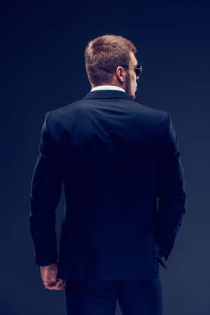 Back view of a Fashion bearded young serious man in sunglasses, luxury suit looking at camera, one hand in pocket 免版税图像