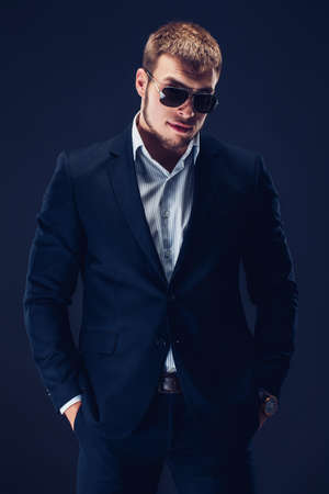 Fashion bearded young serious man in sunglasses, luxury suit looking at camera, hands in pockets