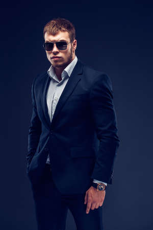 Fashion bearded young serious man in sunglasses, luxury suit looking at camera, one hand in pocket