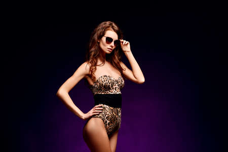 Young sexy woman posing in fashion leopard swimsuit and sunglasses with long hair on dark background 免版税图像