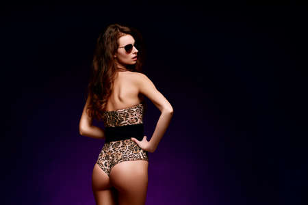 Back view of a young sexy woman posing in fashion leopard swimsuit and sunglasses with long hair on dark background 免版税图像