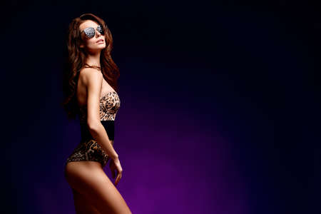Side view of a young sexy woman posing in fashion leopard swimsuit and sunglasses with long hair on dark background