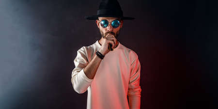 Stylish man in sunglasses puffing the vapor on the black background 免版税图像