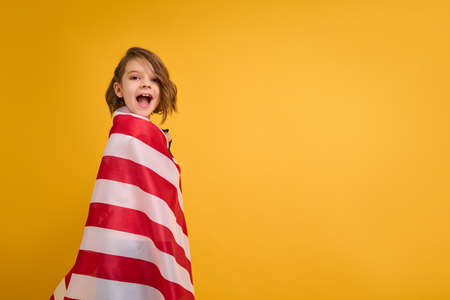 Happy child, cute girl with American flag on yellow studio background. USA celebrate July 4th, independence Day.
