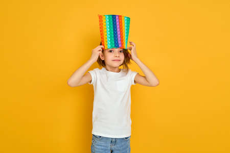 little girl holding pop it antistress toy on yellow background