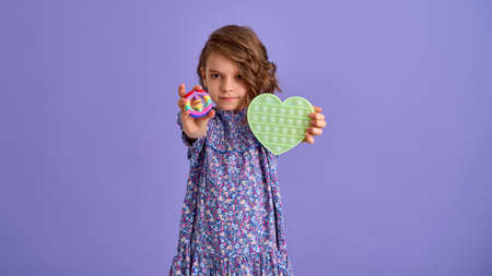 Teen age Girl in blue summer flower print dress holding pop it antistress toy on lavender background, isolate.