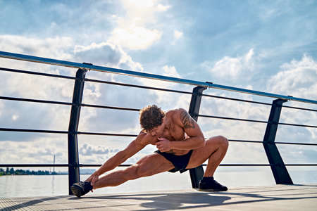 Young muscular tattooed man doing exercises, stretching early in the morning on pier by the sea