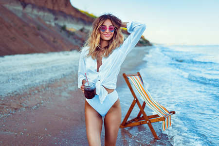 Pretty blonde woman in the shape of a heart sunglasses, white shirt and stripped swimsuit relaxing on beach and drinks coctail. summer vacation concept. Reklamní fotografie