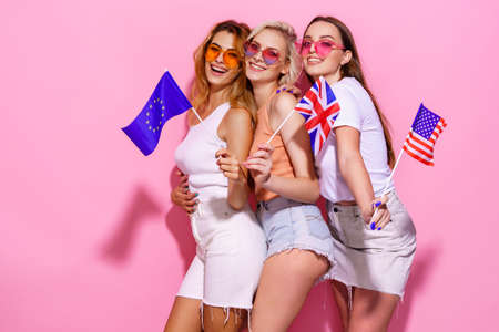 Three girls in summer clothes, glasses holding flags of the European Union, United States and Britain and posing on a pink background in the studio.