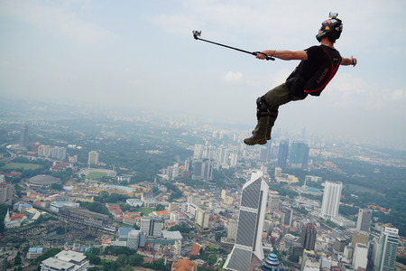 cliff jumping: A BASE jumper in jumps off from KL Tower Editorial