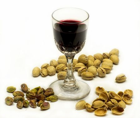Glass of port surrounded by pistachio nuts, some shelled, some in the shells, and empty shells