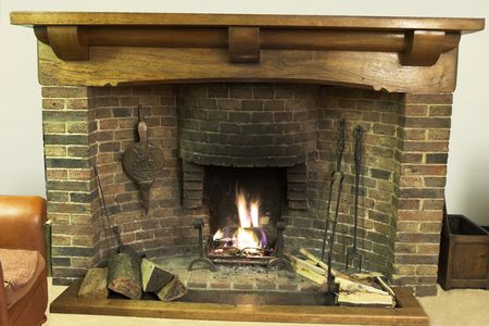 Ancient open log fireplace with wrought iron fire-irons and oak mantlepiece