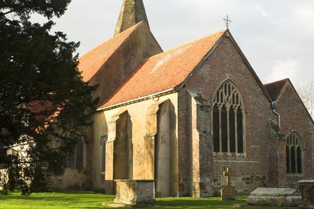 East window of ancient church, seen from outside, with a foreground of ancient tombs photo