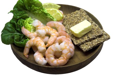 Wooden platter with king prawns, lemon, lettuce and crispbread with butter photo