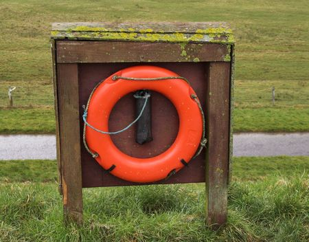 implication: A life-buoy on the top of a dyke, overlooking fields