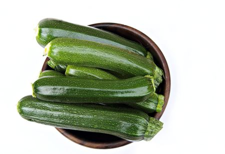 Wooden bowl containing fresh cut courgettes, a.k.a. zucchini Stock Photo