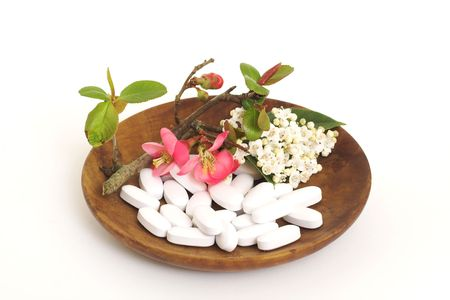 White pills with japonica and lauristinus flowers on a wooden bowl Stock Photo - 2619066