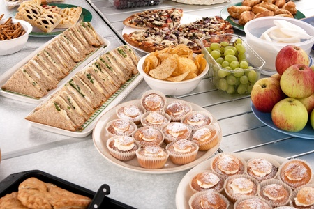Food spread out over table in preparation of a picnic