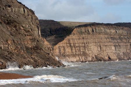Quieter seas now breaking on the cliffs recently fallen Stock Photo - 26584201