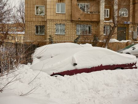 Parked cars buried under white snow on the street