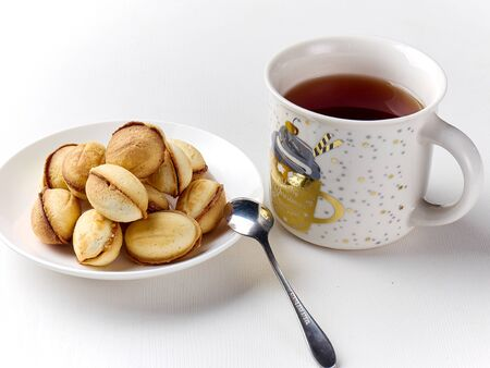 delicious walnut shaped shortbread sandwich cookies filled with sweet condensed milk and chopped nuts and a mug of tea
