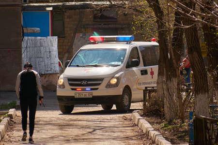 Karaganda, Kazakhstan - 21.04.2020: white Ambulance van calls into the courtyard of a multi-storey building
