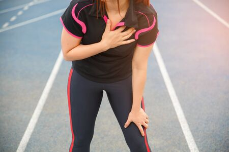 Female runner athlete chest injury and pain. Woman suffering from painful chest or Symptoms of heart disease while running on the blue rubberized running track. Stock Photo