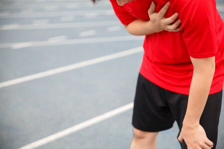 Man runner athlete chest injury and pain. Man suffering from painful chest or Symptoms of heart disease while running on the blue rubberized running track. Stock Photo