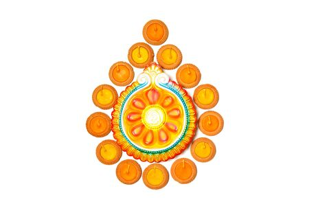 Happy Diwali - Clay Diya lamps lit during Dipavali, Hindu festival of lights celebration. Colorful traditional oil lamp diya on white background.