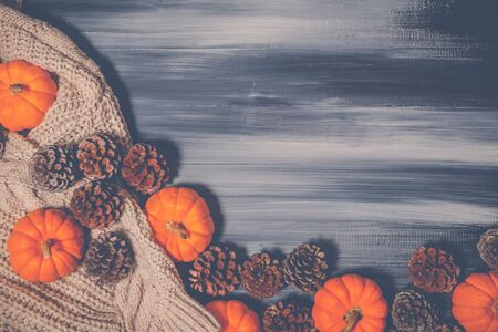 Top view of Halloween day and Thanksgiving day, orange pumpkin, Knitting sweater and pinecone on dark background with copy space for text. Halloween concept, Thanksgiving concepts.